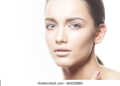 Beautiful face of young caucasian brunette woman with natural lips, make-up, perfect skin and blue eyes isolated on white. Studio portrait.
