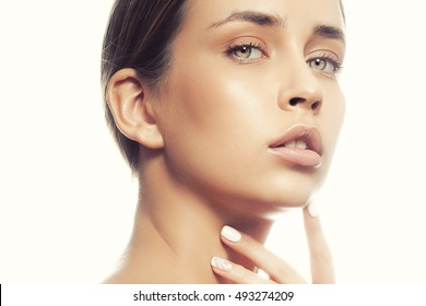 Beautiful face of young caucasian girl with natural make-up, perfect skin and green eyes touching her chin isolated on white background. Studio portrait. Toned
