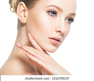 Beautiful face of young caucasian woman with perfect health skin  - isolated on white.  Skin care concept. Female Model touches face.