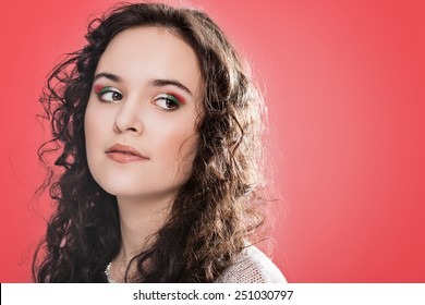 Beautiful face of young woman with clean skin. Girl with long curly hair. Bright eye make-up