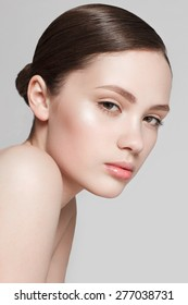 Beautiful face of young woman with clean fresh skin and natural make-up on grey background