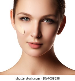 Beautiful face of young woman with cosmetic foundation on a skin. Beauty treatment concept. Makeup artist applying liquid tonal foundation on the face of the woman. Closeup photo of cheek