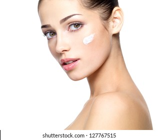 Beautiful face of young woman with cosmetic cream on a cheek. . Skin care concept. Closeup portrait isolated on white.