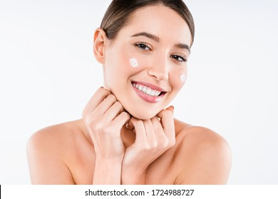 Beautiful face of young woman with cosmetic cream on cheeks . Skin care concept