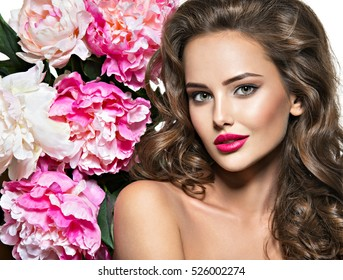 Beautiful face of young  woman over the pink flowers. Portrait of the pretty  healthy skin girl.