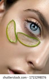 Schönes Gesicht der jungen Frau mit Teilen der Aloe Vera Pflanze auf ihrer sauberen perfekten Haut. Modell mit Aloe Vera natürlichen organischen Pflaster für SPA, Wellness und Hautpflege Konzept. Nahaufnahme, selektiver Fokus.