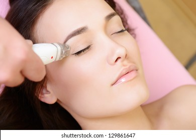 beautiful face of young woman and rejuvenated treatment, lady lies on a couch in a beauty spa getting electrostimulation lifting therapy