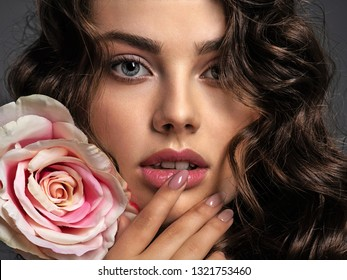 Beautiful face of a young woman with a smoky eye makeup  and rose flower. Sexy and gorgeous brown-haired woman with long curly hair. Portrait of an attractive female posing at studio. Fashion model