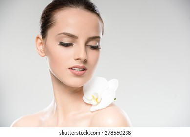 Beautiful face of young woman with a white orchid flower. Skin care treatment.