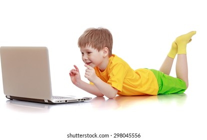 Beautiful fair-haired little boy in a yellow shirt, green shorts lying on the floor and presses the button of the laptop , the boy wonder computer literacy-Isolated on white