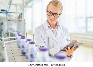 Beautiful fair-haired technologist with clipboard and pen in hands standing at conveyor belt and controlling production process at modern soy milk factory, portrait shot