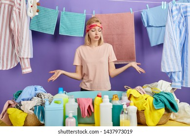 beautiful fair-haired woman shrugging shoulders being sad not knowing how to wash all clothes. isolated blue background, studio shot.