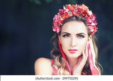 beautiful fairy: filtered image of brunette pretty girl in lotus flower crown and pink makeup posing gracefully on green outdoors copy space background
