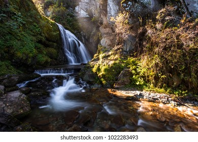 Beautiful fairy mountain waterfall in a fairy forest among rocks at sunset