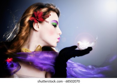 beautiful fairy sending a kiss to a little bird on her palm, profile,  studio shot