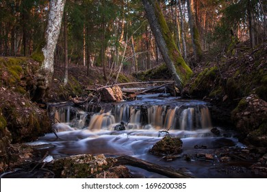 Beautiful fairy tale long exposure waterfall with mossy stones and rocks in the middle of the forest, Kalamecu - Markuzu ravine, Latvia