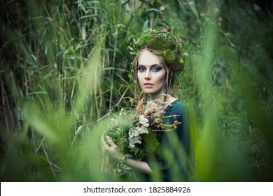 Beautiful fairy witch woman in green grass outdoors. Halloween character or Forest soul