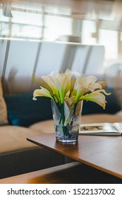 Beautiful fake flowers sitting on a table in front of a modern sofa seen  through a prism with reflections