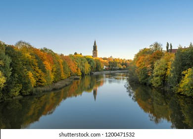 Beautiful fall foliage and Aura river against clear blue sky with Turku Cathedral in background in Turku, Finland, Autumn 2018