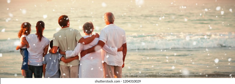 Beautiful family at the beach against snow falling