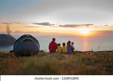 Beautiful family, camping on a hill, enjoying the sunset view in Exmoor National Park on a summer day