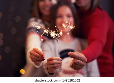Beautiful family celebrating Christmas and holding sparklers - Shutterstock ID 1493281862