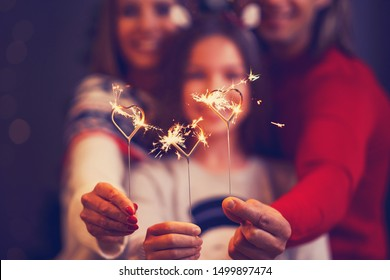 Beautiful family celebrating Christmas and holding sparklers