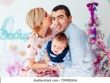 Beautiful family with a child sits before a pink Christmas tree