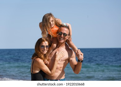 Beautiful family consisting of father, mother and a daughter relaxes at the beach