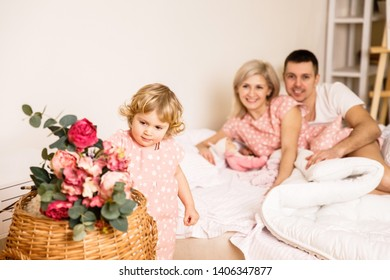 beautiful family dad mom and daughter in pajamas having fun in the bedroom on the bed in a bright apartment
