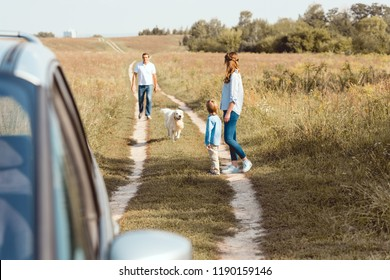 beautiful family with dog walking by field road together with car on foreground