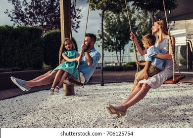 Beautiful family is having fun outside. Parents with children riding on a swing. Mom with dad are playing with their little daughter and son on a terrace with swings.