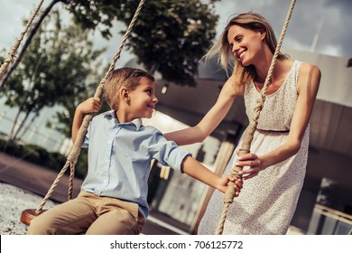 Beautiful family is having fun outside. Parents with children riding on a swing. Mom is playing with her little son on a terrace with swings.