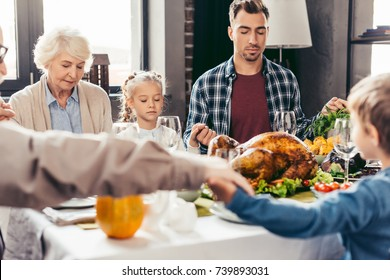 beautiful family holding hands and praying on thanksgiving before holiday dinner