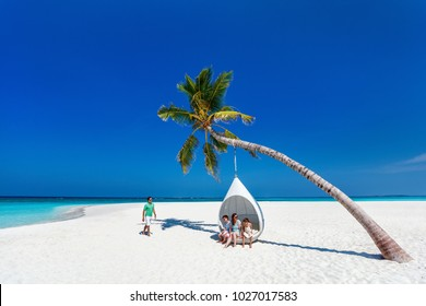 Beautiful family with kids on a tropical beach during summer vacation