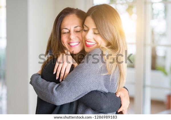 Hermosa familia de madre e hija juntas, abrazándose y besándose en casa