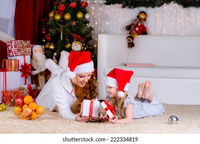 beautiful family mother and her baby on the floor near the Christmas tree on Christmas Eve open box with a gift