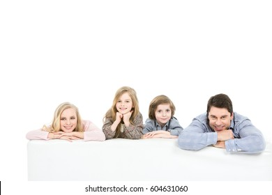 Beautiful family on the bed laughing and enjoyed isolated on white background.