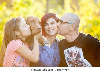 Beautiful family on the grass in park playing with their dog. Animal lovers