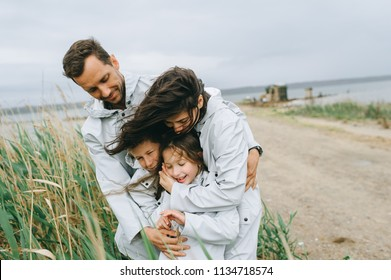 Beautiful family portrait dressed in raincoat near the lake