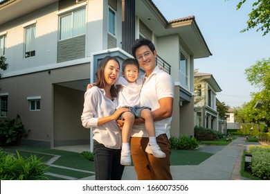 Beautiful family portrait smiling outside their new house with sunset, this photo canuse for family, father, mother and home concept