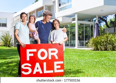 Beautiful family portrait standing outside their new house smiling, hold for sale sign