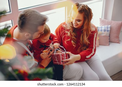 Beautiful family sitting at home. Cute mother in a red sweater. Little boy with handsome father