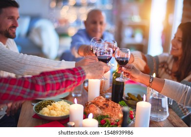 Beautiful family smiling happy and confident. Eating roasted turkey and toasting with cup of wine celebrating Thanksgiving Day at home