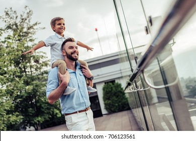 Beautiful family is spending time together  outside. Dad and his little son are having fun on a roof terrace with view on a city. Sitting on father's shoulders and smiling.