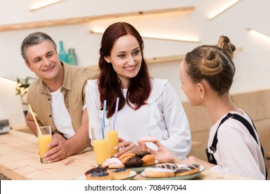 beautiful family standing at bar counter in cafe