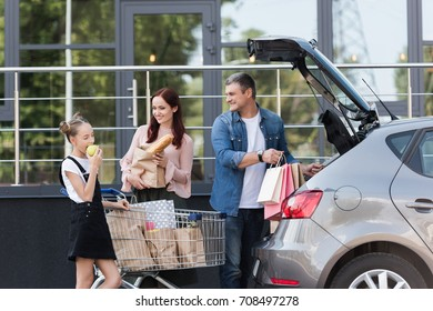 beautiful family with teen daughter packing shopping bags in car