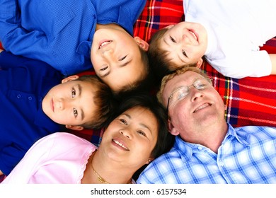 Beautiful family of Thai and European inter marriage made up of three lovely boys and the parents, outdoor.