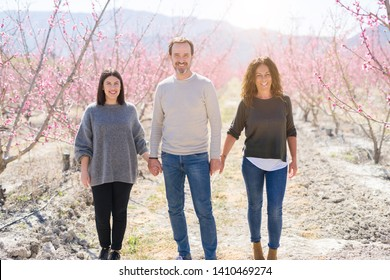 Beautiful family of three smiling cheerful walking toghether on peach garden with pink petals enjoying sunny day of spring