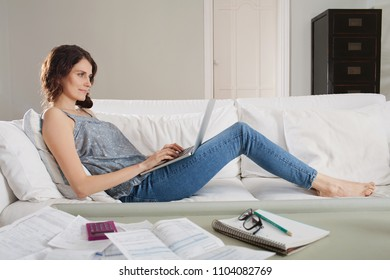 Beautiful family woman working out home finances using laptop computer, with invoices and paperwork on sofa, living room interior. Middle age female economics accounts, cash flow expenses, indoors.